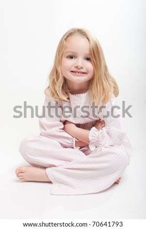 Cute little blonde girl in her pajamas sitting on the floor