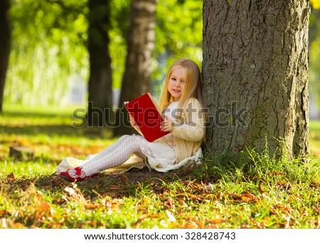 Cute little blonde girl sit near tree, read favorite book and dream