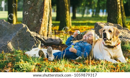 Stock Photo Cute little blonde girl sitting with dog on the grass in the forest