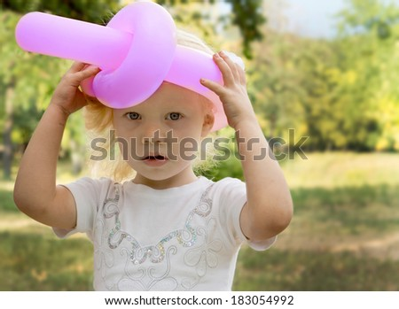 Cute little blonde girl with a serious expression wearing a pink hat made from a twisted and tied balloon with her hands raised holding it on