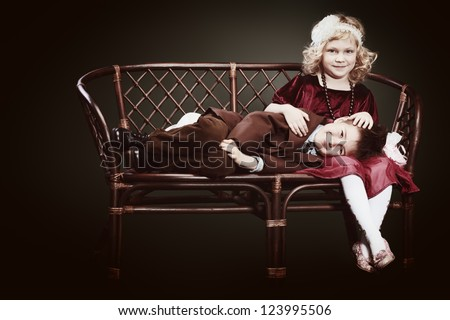 Cute little boy and charming little lady sitting on a bench. Retro style.