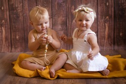 Cute little boy and girl under one year old sit and play with wooden toys on a dark wooden background. Healthy childhood