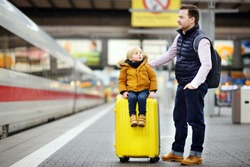 Cute little boy and his father waiting express train on railway station platform. Travel, tourism, winter vacation and family concept. Man and his son together.