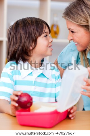 Cute little boy and his mother preparing his snack in the kitchen
