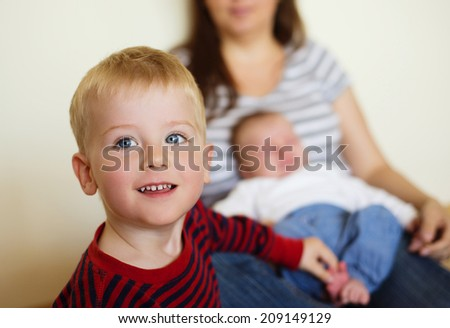 Cute little boy and his mother with his baby brother at the background