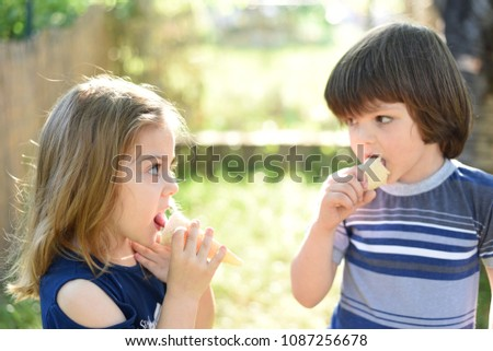 Cute little boy and little girl eating ice cream at sunset. Little boy and little girl eat ice cream in close up face feeling delicious. Kids with dirty face eating ice cream #1087256678