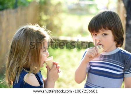 Cute little boy and little girl eating ice cream at sunset. Little boy and little girl eat ice cream in close up face feeling delicious. Kids with dirty face eating ice cream