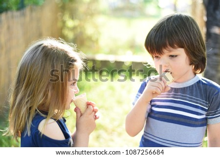 Cute little boy and little girl eating ice cream at sunset. Little boy and little girl eat ice cream in close up face feeling delicious. Kids with dirty face eating ice cream #1087256684