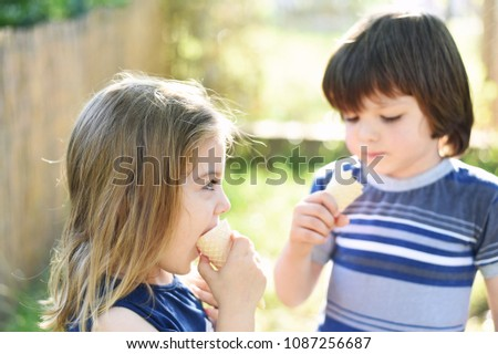 Cute little boy and little girl eating ice cream at sunset. Little boy and little girl eat ice cream in close up face feeling delicious. Kids with dirty face eating ice cream #1087256687