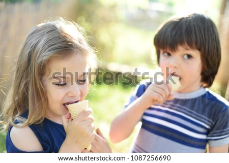 Cute little boy and little girl eating ice cream at sunset. Little boy and little girl eat ice cream in close up face feeling delicious. Kids with dirty face eating ice cream #1087256690