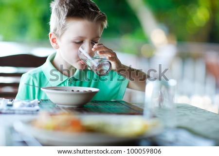 Cute little boy at restaurant drinking water