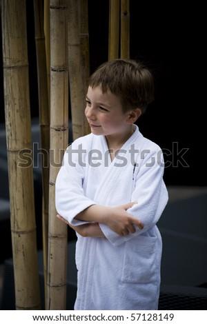 Cute little boy at spa wearing bathrobe