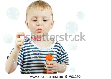 cute little boy blowing bubbles on white background