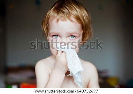 Cute little boy blowing his nose into a handkerchief.