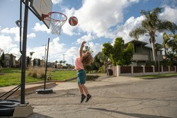 Cute little boy child jumping with basket ball for shot. Cute child playing basketball.