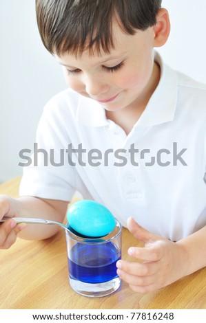 Cute little boy coloring Easter egg