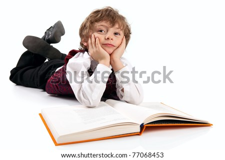 Cute little boy daydreaming while reading book