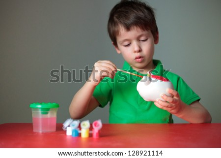 Cute little boy diligently painting his piggy toy indoors