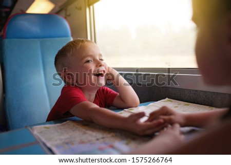 Cute little boy discussing vacations with his sister during their travelling by train, transport, happy family vacation and summertime, lifestyle inside portrait