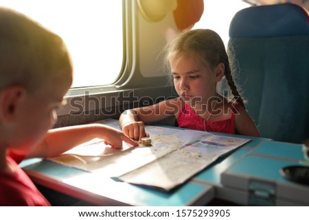 Cute little boy discussing with his smiling sister their economy vacations during travelling time by train, transport, happy family vacation and summertime, lifestyle inside portrait