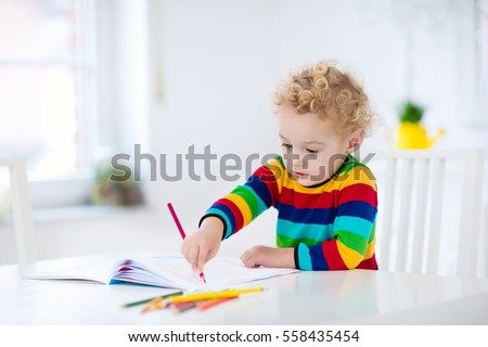 Cute little boy doing homework, reading a book, coloring pages, writing and painting. Children paint. Kids draw. Preschooler with books at home. Preschoolers learn to write and read. Creative toddler. #558435454