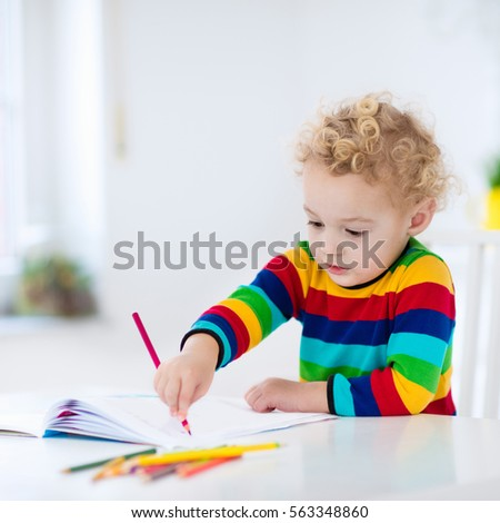 Cute little boy doing homework, reading a book, coloring pages, writing and painting. Children paint. Kids draw. Preschooler with books at home. Preschoolers learn to write and read. Creative toddler. #563348860