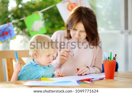 Cute little boy drawing and painting with colorful markers pens at kindergarten. Creative kid painting at playschool. Development toys for preschooler children #1049771624
