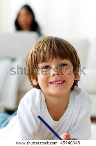 Cute little boy drawing lying on the floor in the living-room