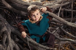 Cute little boy dressed as a knight playing in the woods