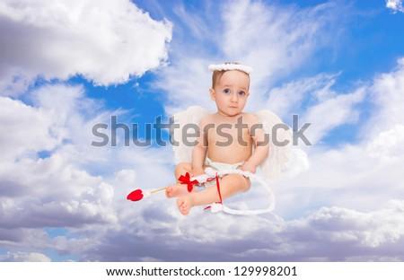 Cute little boy dressed as Cupid on blue sky