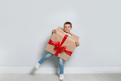Cute little boy dressed as gift box near white wall. Christmas suit