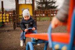 Cute little boy dressed in a warm jacket and hat riding on the swing with parents