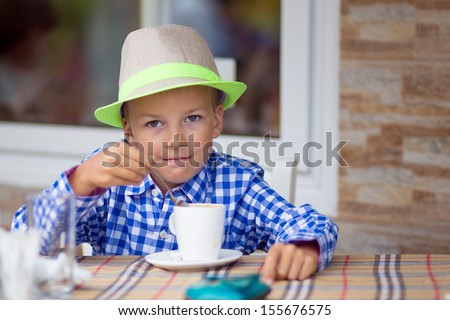Cute little boy drinking hot chocolateat indoor cafe - stock photo