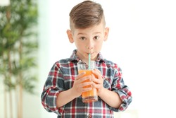 Cute little boy drinking juice at home
