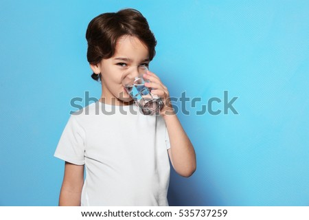 Shutterstock Cute little boy drinking water from glass on blue background