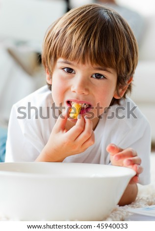 Cute little boy eating chips lying on the floor in the living-room