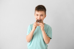 Cute little boy eating chocolate on light background