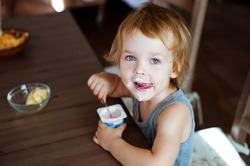 Cute little boy eating yogurt.