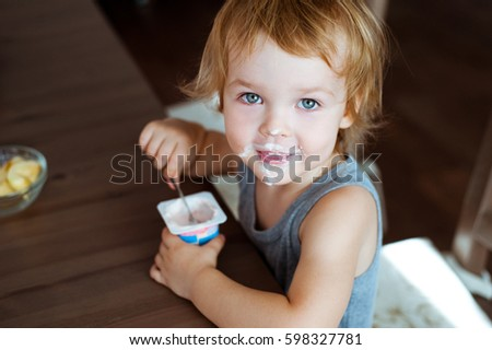 Cute little boy eating yogurt.