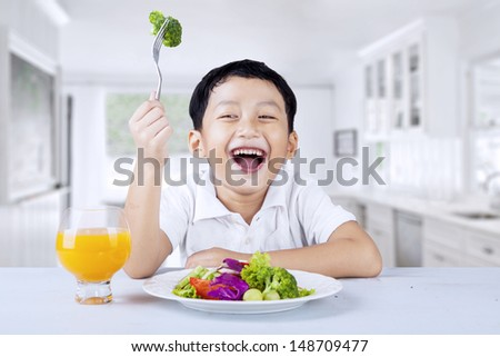 Cute little boy eats vegetable salad using fork, shot in the kitchen