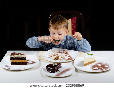 Cute little boy enjoying a treat of party cakes hungrily gulping down a big mouthful with slices of a variety of different cakes displayed in front of him