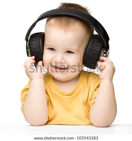 Cute little boy enjoying music using headphones, isolated over white