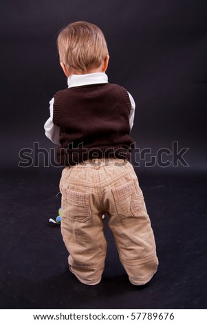 Cute little boy from behind over black background