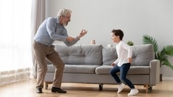 Cute little boy grandson having fun dancing with old elderly grandpa in living room, happy two generation active family senior grandfather and small grandchild playing enjoying time together at home