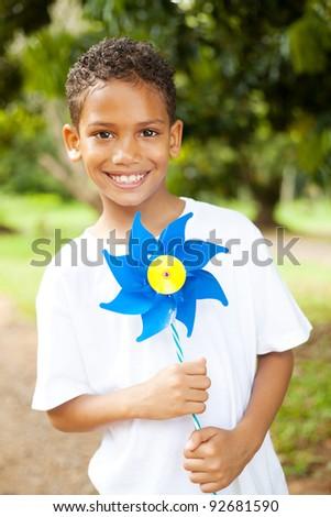 cute little boy holding a pinwheel outdoors