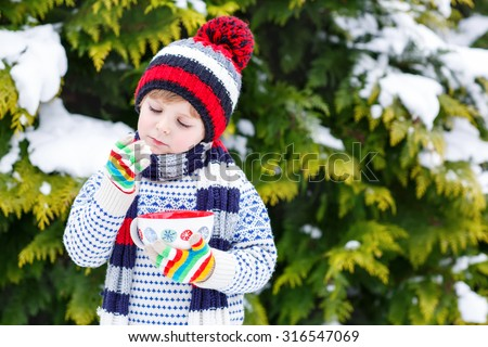 Cute little boy holding big cup with snowflakes and hot cocoa and chocolate drink and marshmallows. Kid boy in winter sweater, hat, long warm scarf and colorful gloves. On cold snowy winter day.