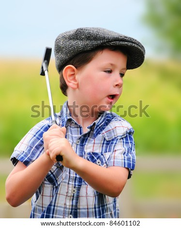 Cute little boy in a driving hat playing with a golf club