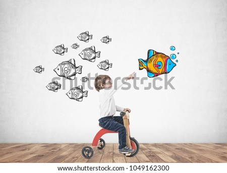 Cute little boy in a white shirt and dark blue jeans is riding a tricycle and showing with his finger. A concrete wall background with a choice and leadership sketch on it.