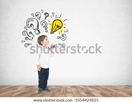Cute little boy in a white shirt and dark jeans holding a marker and looking upwards. Question marks and a light bulb on a concrete wall. Mock up