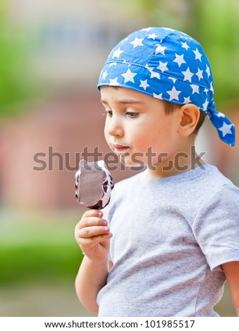 Cute little boy in bandana eats ice cream - stock photo